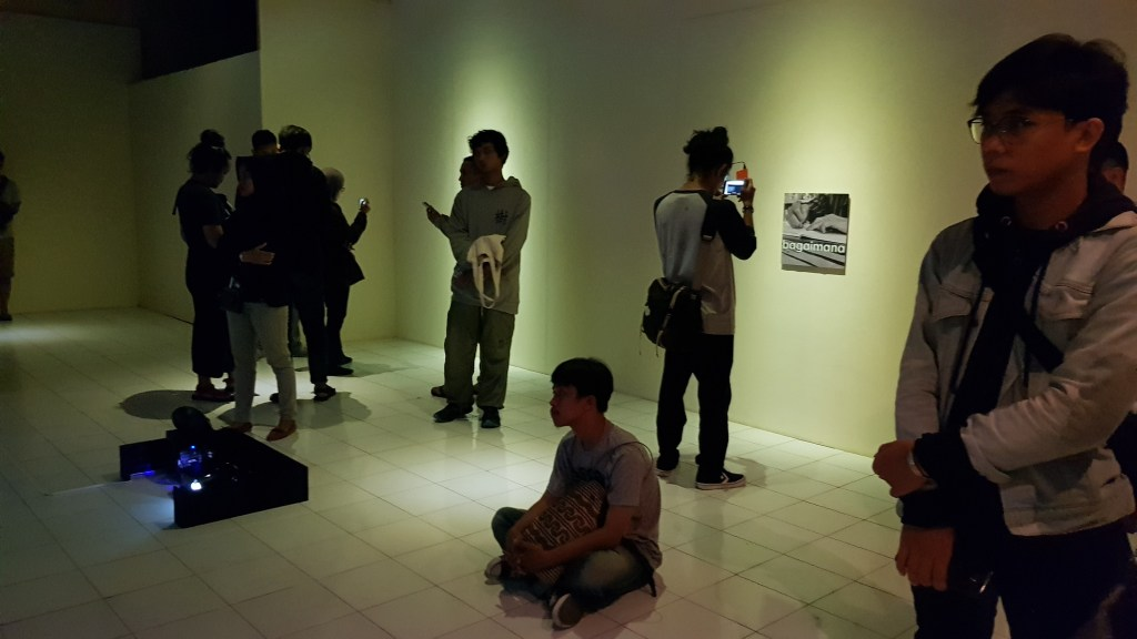 In the gallery space, viewers look at the videos and projections while one frames an AR marker on his mobile phone.