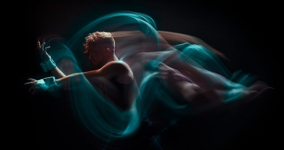Against a black background, two people wearing MiMU Gloves are dancing. Blurry lines of turquoise light track the movement of their hands.