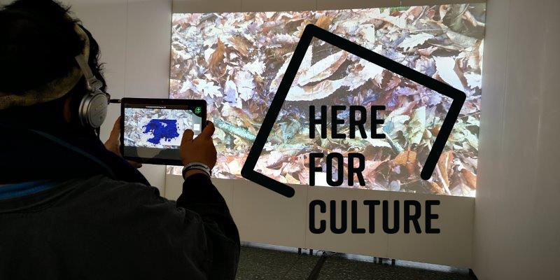 A woman looking at a projection with the words 'here for culture' through a tablet screen