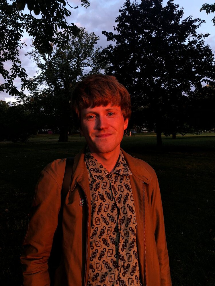 Calum Perrin stands in front of a park drenched in golden sunlight.